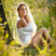 Pretty young blonde girl in white dress sitting in grass — Stock Photo #13349783