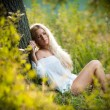 Pretty young blonde girl in white dress sitting in grass — Stock Photo #13349791