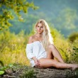 Pretty young blonde girl in white dress sitting in grass — Stock Photo