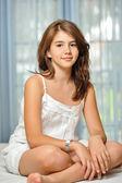 Ritratto di sorridente bella ragazza teenager a casa in abito bianco e rilassarsi sul comodo letto. interni di lusso. — Foto Stock