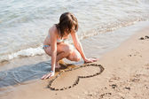 Girl at the beach drawing hearts on a sand — Stock Photo