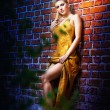 Charming young blonde woman in yellow dress near the brick wall — Stock Photo #14025687