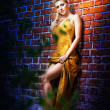 Charming young blonde woman in yellow dress near the brick wall — Stock Photo