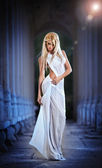 Beautiful blonde angel with white light wings and white veil posing outdoor — Foto de Stock