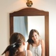 A beautiful teen girl studies her appearance as she looks into the mirror at her beautiful young reflection. Teen girl happy with their appearance in the mirror — Stock Photo #19656613