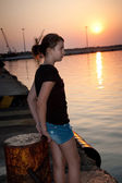 Pretty teen girl sitting on a dock looking into the sea at sunset — Stock Photo