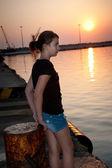 Muito adolescente sentado numa doca, olhando para o mar ao pôr do sol — Foto Stock