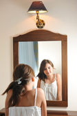 A beautiful teen girl studies her appearance as she looks into the mirror at her beautiful young reflection. Teen girl happy with their appearance in the mirror — Photo