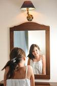 Une belle teen fille étudie son apparence comme elle regarde dans le miroir à son beau reflet de jeune. teen fille heureuse avec leur apparence dans le miroir — Photo
