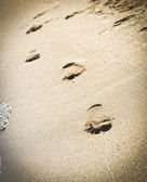 Foot prints at sand in summer sunrise on tropical beach — Stock Photo