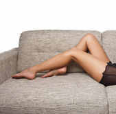 Long Woman legs in stockings on sofa. sexy women legs on sofa . — Stock Photo