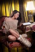 Dziewczyna siedzi na krześle, czytając książkę i uśmiechając się — Zdjęcie stockowe