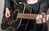 Female hand playing acoustic guitar — Stock Photo