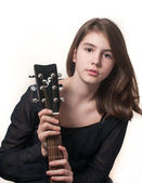 Young brunette teen girl playing acoustic guitar isolated on white. — Stock Photo