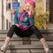 Young fashionable beautiful girl with pink cap looking around in the city — Stock Photo