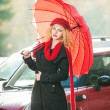 .Beautiful fashionable young girl with red umbrella in the street — Stock Photo