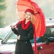 .Beautiful fashionable young girl with red umbrella in the street — Stock Photo #20690649