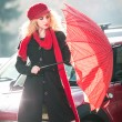 .Beautiful fashionable young girl with red umbrella in the street — Stock Photo #20690663