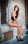 Roztomilá brunetka s černou podprsenku pózuje na ulici ve městě — Stock fotografie