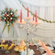 Candlestick with candles and floral arrangements on wedding ceremony detail - Stock Photo