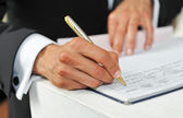 Business man signing a contract on a white table. — Stock Photo