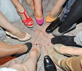 Legs and shoes standing in a circle in tile — Stock Photo