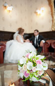 Wedding details - young marrieds behind a wedding bouquet in a room — Stock Photo
