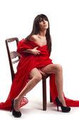 Portrait eines schönen Mädchens sitzend auf Stuhl auf einem weißen Hintergrund Closeup und roten Schleier — Stockfoto