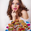 Portrait of young surprised woman eating cakes isolated on white background . Big plate with many cakes — Stock Photo