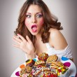 Portrait of young surprised woman eating cakes isolated on white background . Big plate with many cakes — Stock Photo #22651419