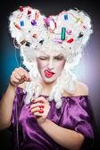 Senhora focada com acessórios para bordar em sua cena de wig.vintage da bela dama com carretel coloridas em Girl a peruca com acessórios de costura no cabelo tentando uma agulha da linha — Fotografia Stock