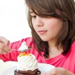 Funny teen  brunette girl eating cake on the white background — Stock Photo