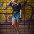 Beauty girl posing fashion near red brick wall on the street .Young woman with sun glasses against a graffiti wall — Stock Photo #22880920