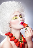 Creative makeup beauty shot of model with strawberries, artistic edit .Woman with strawberry necklace, wig and makeup professionally posing in studio.Beauty with strawberry — Stock Photo