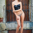 Sexy girl in bikini posing fashion near red brick wall on the street.Shot of a sexy high fashion woman posing outdoor. Cute brunette with black bra posing on a city street — Stock Photo