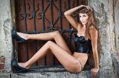 Ragazza sexy in bikini in posa moda vicino muro di mattoni rossi sul street.shot di una donna sexy alta moda in posa all'aperto. brunetta carina con reggiseno nero in posa su una strada di città — Foto Stock