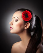 Fashion Brunette Girl with Flower isolated on textured background.Profile of makeup woman with red flower in hair on textured background.Young beautiful girl with red flower in hair posing in studio. — Stock Photo