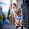 Girl short skirt and bag walking on street.Young European Girl in Urban Setting.sexy woman dressed provocatively and posing on street.Blonde attractive woman with interesting hair walking in the city — Stock Photo #23966135