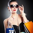 Woman with glasses holding shopping bags against a black background.Style beauty girl with shopping bags.Portrait of stunning young woman in sunglasses carrying multicolored shopping bags  — ストック写真