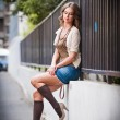 Young European Girl in Urban Setting.sexy woman dressed provocatively and posing on street.Blonde attractive woman with interesting hair and long legs resting on the edge of a wall — Stock Photo