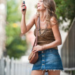 Fashion blonde girl with short skirt at playing with mobile phone.Young attractive woman talking on a cell phone in a street.happy young woman play by mobile phone on the street — Stock Photo