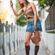 Fashion blonde girl with short skirt at playing with mobile phone.Young attractive woman talking on a cell phone in a street.happy young woman play by mobile phone on the street — Stock Photo #24014155