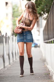 Fashion girl with short skirt , bag and high heels walking on street.attractive woman with interesting hair walking in the city.Walking fashion model in blue short skirt with long sexy legs . — Stock Photo