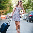 Beautiful woman with suitcases crossing the street in a big city.Beautiful woman with sunglasses on a street and holding a suitcase. young woman with long legs in a urban setting — Stock Photo