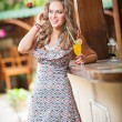 Постер, плакат: Woman drinking glass orange juice Blonde with a glass of orange juice with straw outdoor Portrait of happy young smiling woman drinking fresh orange juice in the park