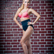 Girl in swimsuit posing provocatively in front of a brick wall.young model posing in front of Brick wall.Posing pretty.Beautiful model standing near red brick wall - Stock Photo