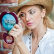 Beautiful woman with straw hat and mirror .Young woman looking in cosmetic mirror .Good looking beautiful woman doing make-up in front of mirror. — Stock Photo