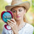 Beautiful woman with straw hat and mirror .Young woman looking in cosmetic mirror .Good looking beautiful woman doing make-up in front of mirror. — Stock Photo #25066367