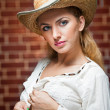 Attractive blonde girl with straw hat and white blouse.Beautiful young woman with straw hat and white kaftan against a brick wall.Gorgeous blond haired blue eyes while wearing a straw cowboy hat. — Stock Photo