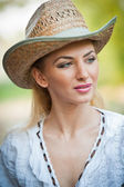 Attractive blonde girl with straw hat and white blouse.Beautiful young woman with straw hat and white kaftan outdoor.Gorgeous blond haired blue eyes while wearing a straw cowboy hat. — Stock Photo